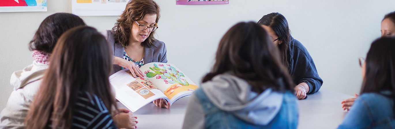 Teacher showing a book to students
