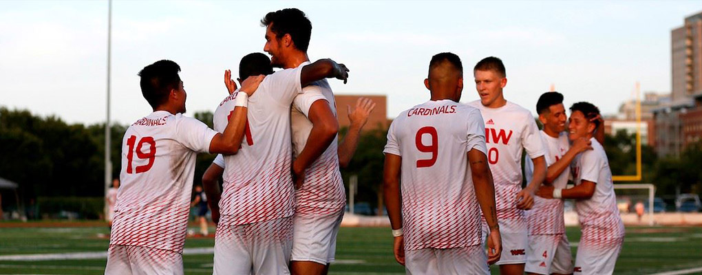 Men's soccer players gather in a huddle