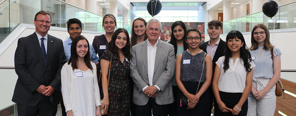 Mr. Carlos Alvarez poses for a photo with UIW students and Dr. Evans