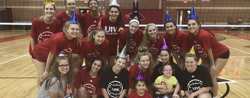 Volleyball team wears party hats and poses for a photo on the court