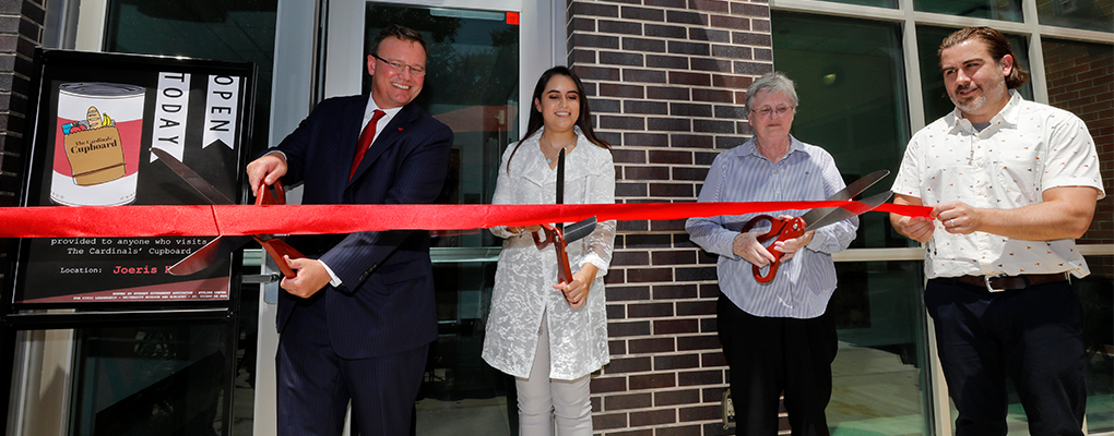 UIW community members cut red ribbon with giant scissors