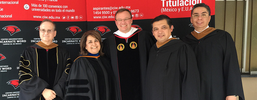 Dr. Evans and Dr. Barbara Naranjo pose for a photo with faculty and staff of CUIW at their commencement ceremony
