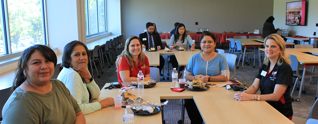 UIW employees sit at a table with food and smile
