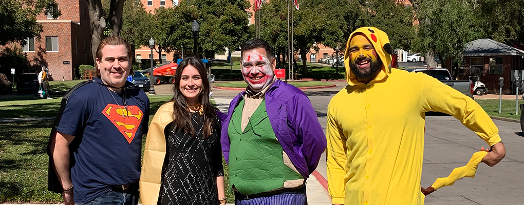 UIW community members dressed in Halloween costumes pose for a photo together
