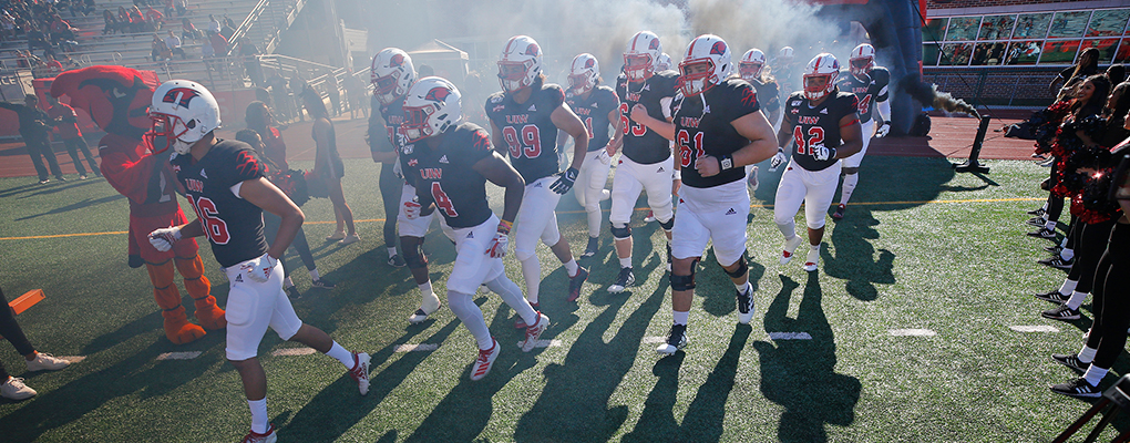 UIW Football players run onto the field through a cloud of smoke surrounded by cheerleaders