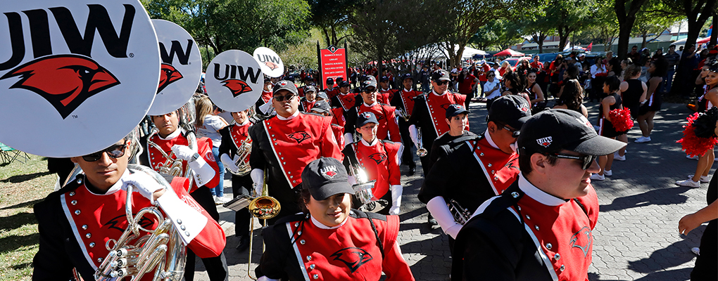 The UIW Marching Band marches in uniform holding their instruments