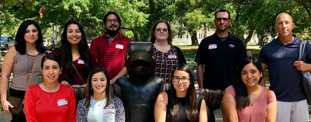 New UIW employees pose for a photo at a bench in the shape of the school's mascot
