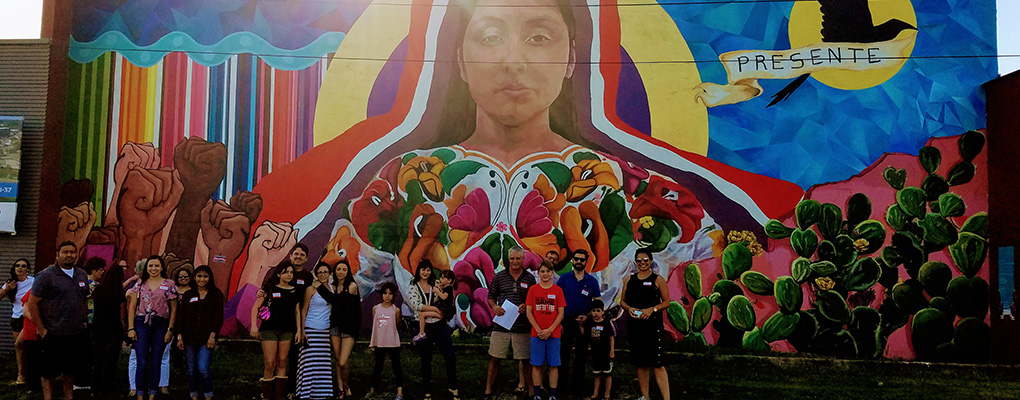 UIW community members pose in front of a large painted mural of a 20-year-old indigenous woman from Quetzaltenango, Guatemala