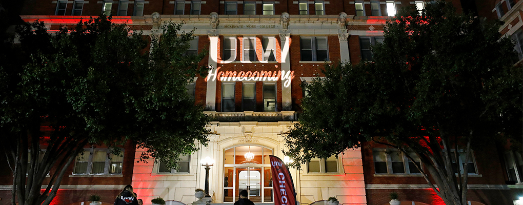 "The words ""UIW Homecoming"" are illuminated on the outside wall of a red brick building"