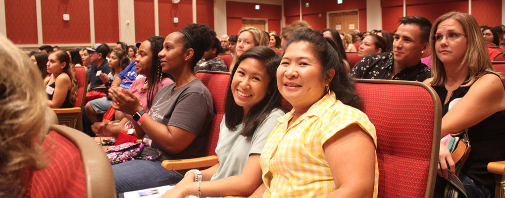 A new student sits by her mother in the UIW Concert Hall for freshman orientation