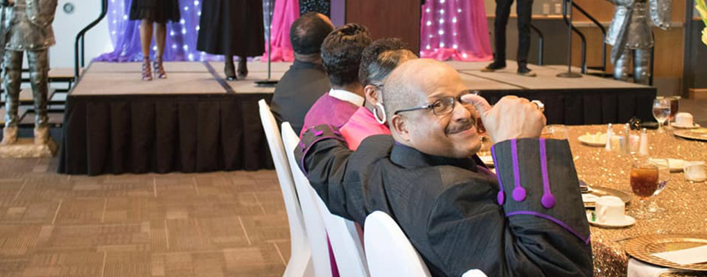 "Bishop Trevor Alexander sits at his reception and gives a ""thumbs up"" to the camera"