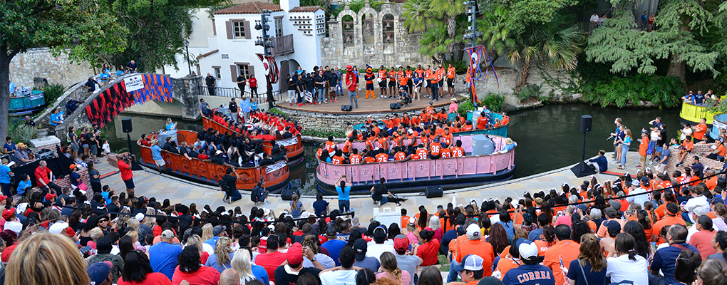 Crowds of people wearing red and black and orange and red sit at the Arneson River Theater as river barges with UIW and UTSA teams float in the San Antonio River