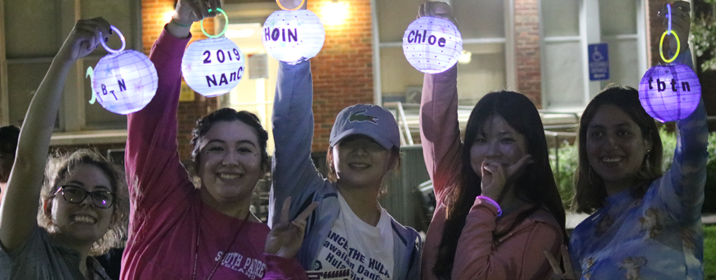 A group of students hold up lit lanterns
