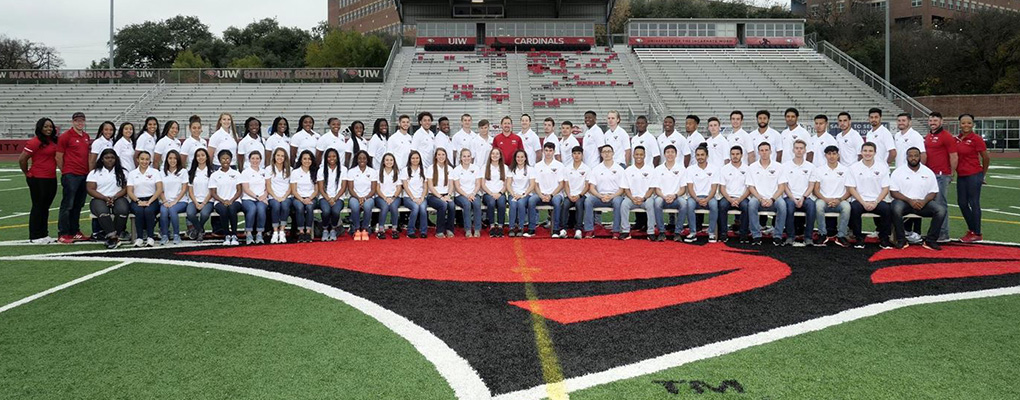 The UIW track and field time pose for a group photo on the football field