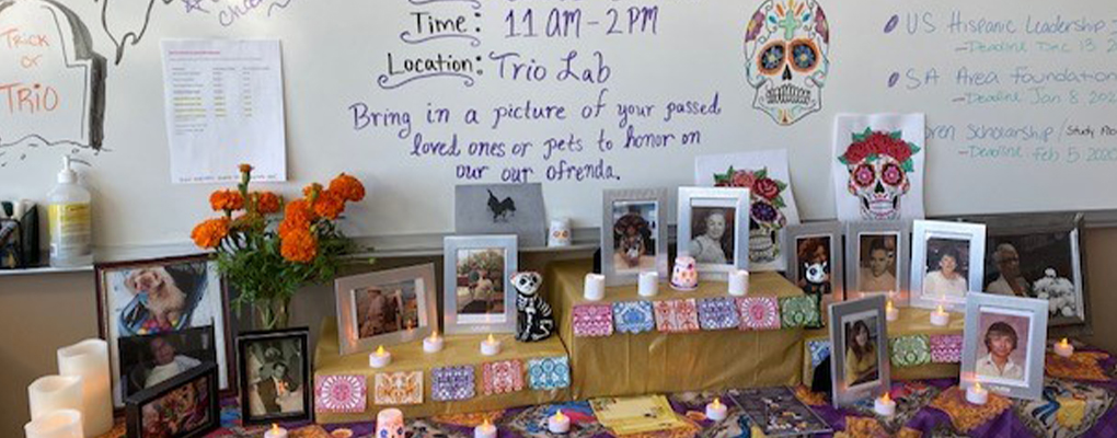 An ofrenda for Dia de los Muertos with photos, candles and traditional decorations
