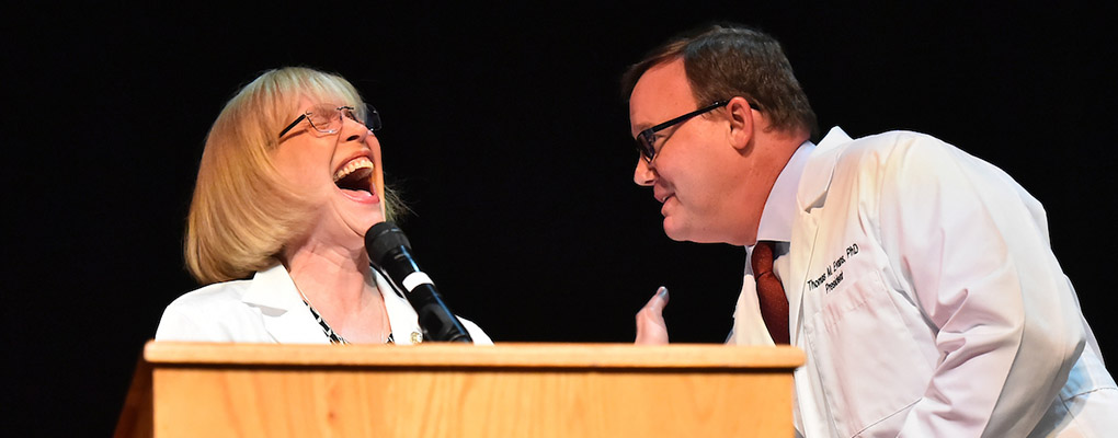 Dr. Evans and Dr. Robyn Phillips-Madson share a laugh at the podium