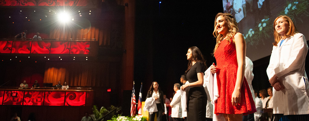 A female student stands on stage with her white coat draped over her arm